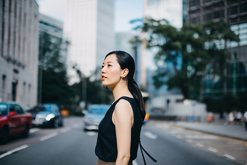 Beautiful young woman commuting to work in urban downtown city street in the morning - gettyimageskorea