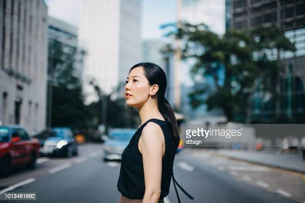 Beautiful young woman commuting to work in urban downtown city street in the morning