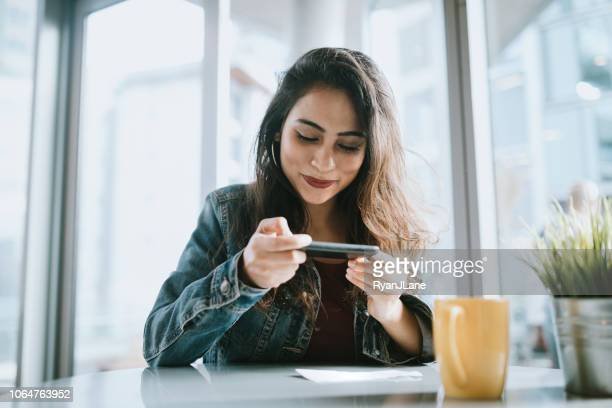 beautiful young woman depositing check with smartphone - portable information device stock pictures, royalty-free photos & images