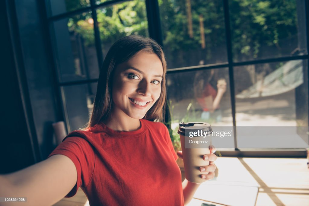 Beautiful young woman doing selfie on the front camera of her smartphone and holding a paper cup with a drink : Stock Photo