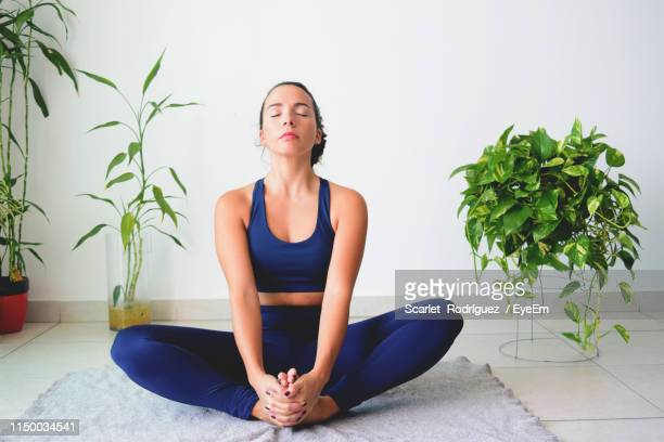 beautiful young woman doing yoga on exercise mat at home - home workout stock pictures, royalty-free photos & images