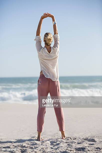 beautiful young woman doing yoga on sunny beach - arms raised stock photos and pictures