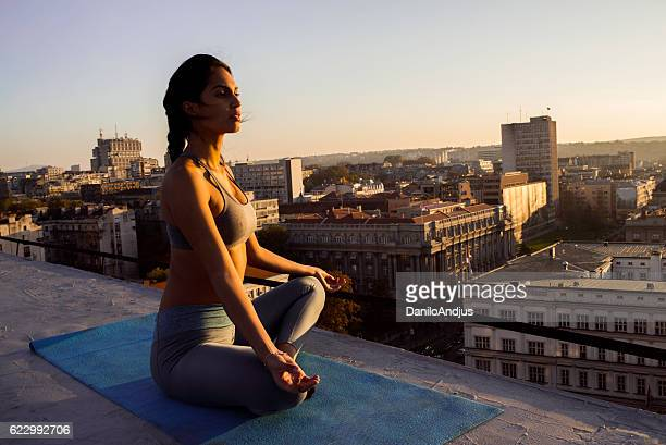 beautiful young woman doing yoga on the rooftop