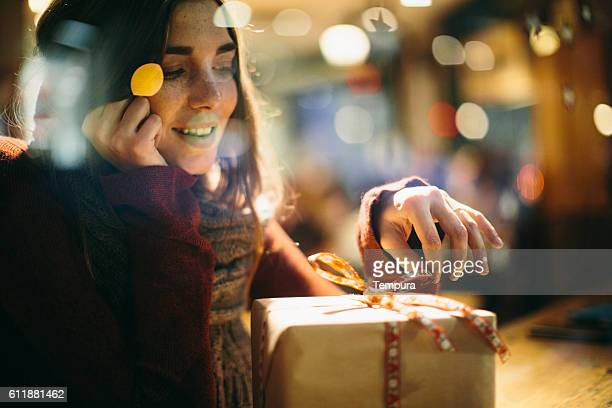 Beautiful young woman dreaming with christmas present