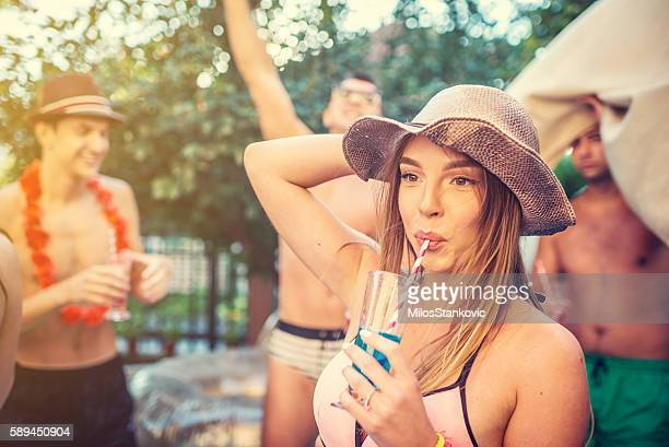Beautiful young woman drink coctail at pool party