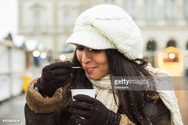 Schöne junge Frau trinken heißen Schokolade auf der Straße