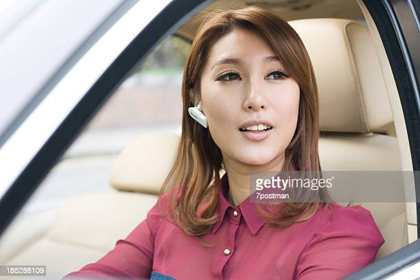 Beautiful Young Woman Driving Car Talking on Bluetooth Headset