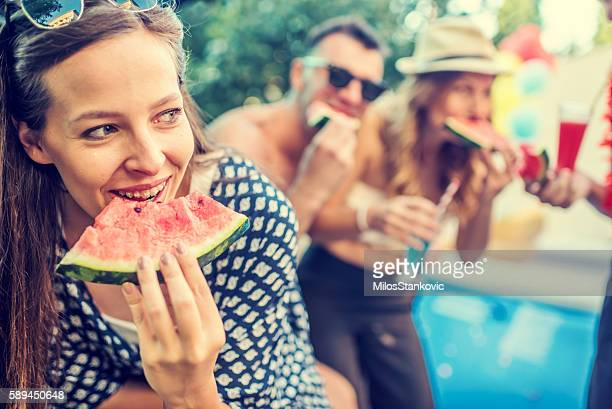 Beautiful young woman eat watermelon at pool party