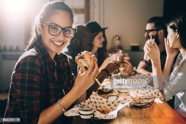 beautiful young woman eating a burger and looking at the camera