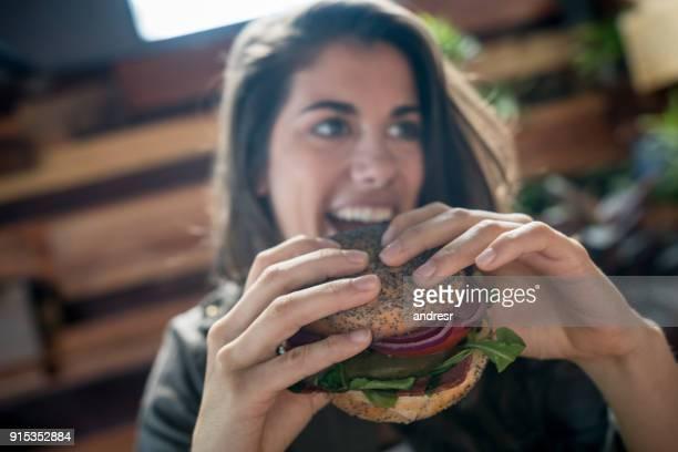 Hermosa mujer joven comer un bagel vegetariano mirando lejos