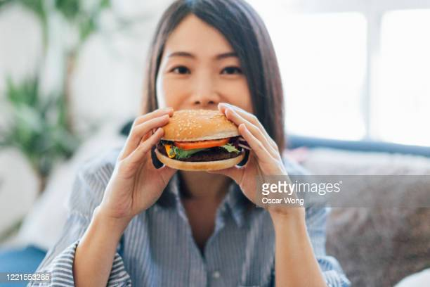 beautiful young woman eating burger - ready to eat stock pictures, royalty-free photos & images