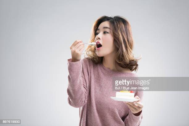 Beautiful young woman eating cake