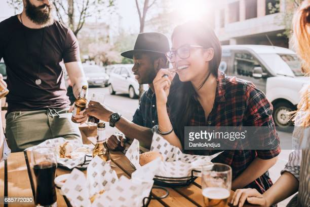 beautiful young woman eating outdoors with her friends