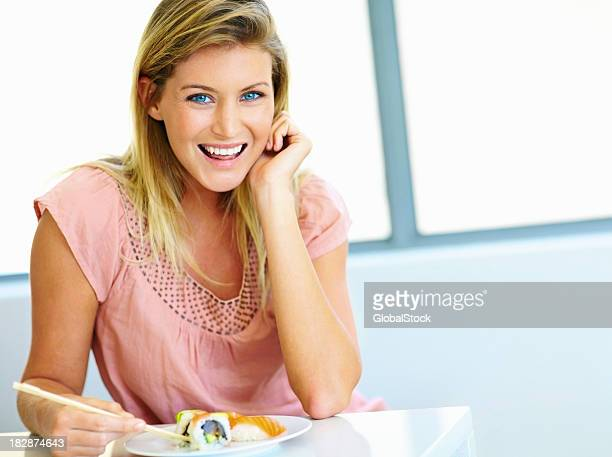 Beautiful young woman eating sushi