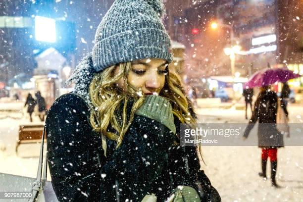 Schöne junge Frau am ersten Schnee genießen