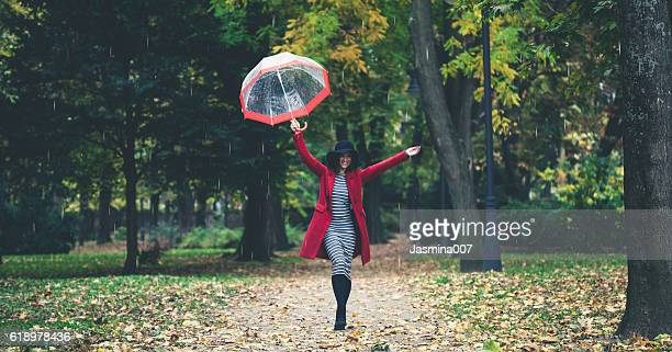 beautiful young woman enjoying a rainy day - september stock-fotos und bilder