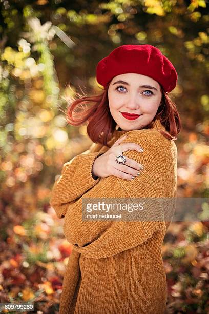 Beautiful young woman enjoying autumn wind in nature.