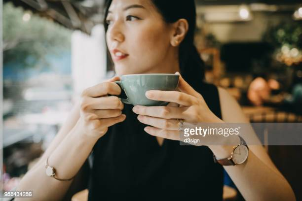 beautiful young woman enjoying coffee in cafe - asian drink stock photos and pictures
