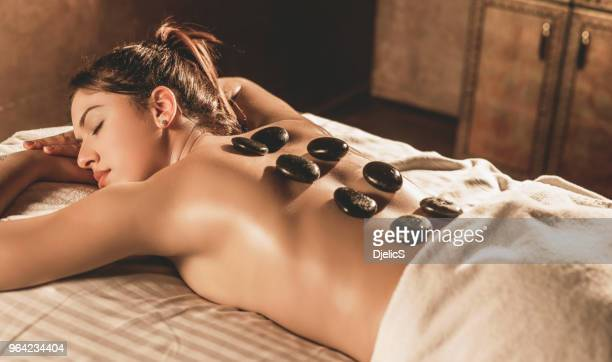 beautiful young woman enjoying hot stone therapy. - one young woman only stock pictures, royalty-free photos & images