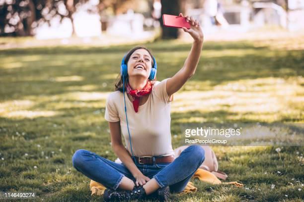 mooie jonge vrouw genieten in de muziek in de natuur - real people stockfoto's en -beelden
