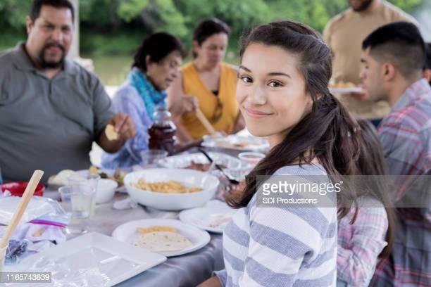家族の集まりで食事を楽しむ美しい若い女性 - ポットラック ストックフォトと画像