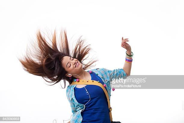 Beautiful young woman enjoying music white swinging hair over white background