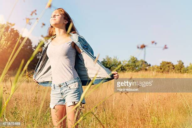 Beautiful young woman enjoying nature in wheat field.