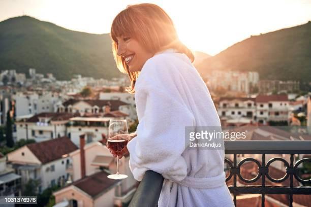 ワインのグラスを持ってバルコニーで楽しむ美しい若い女性 - バスローブ ストックフォトと画像