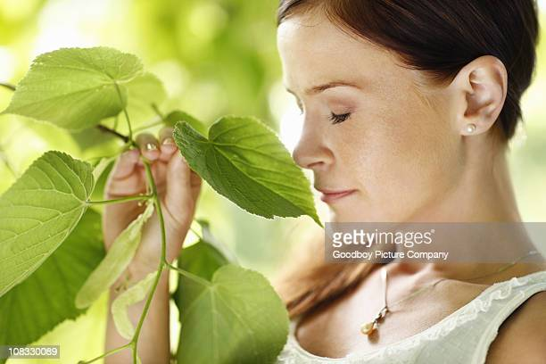Beautiful young woman enjoying the fragrance of leaves