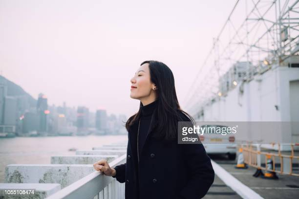 beautiful young woman enjoying the tranquility and gentle wind breeze with eyes closed by the harbour - 雰囲気 ストックフォトと画像