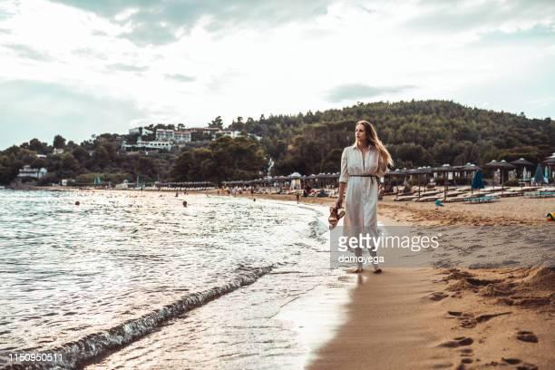 美しい若い女性がビーチで散歩を楽しむ - サンドレス ストックフォトと画像
