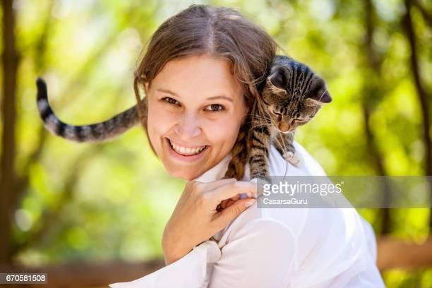 Belle jeune femme jouissant avec son chat sur les épaules