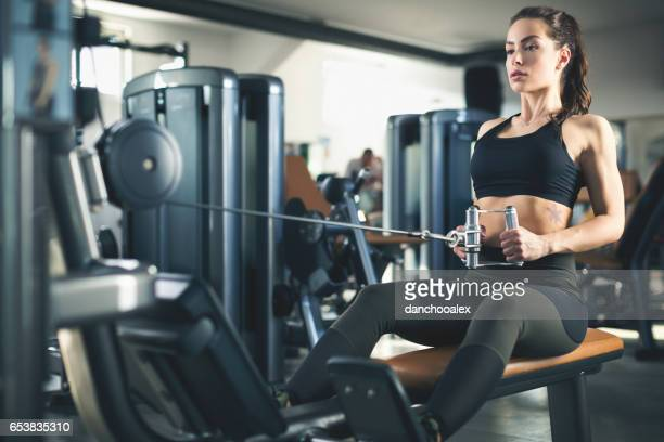 Beautiful young woman exercising at gym