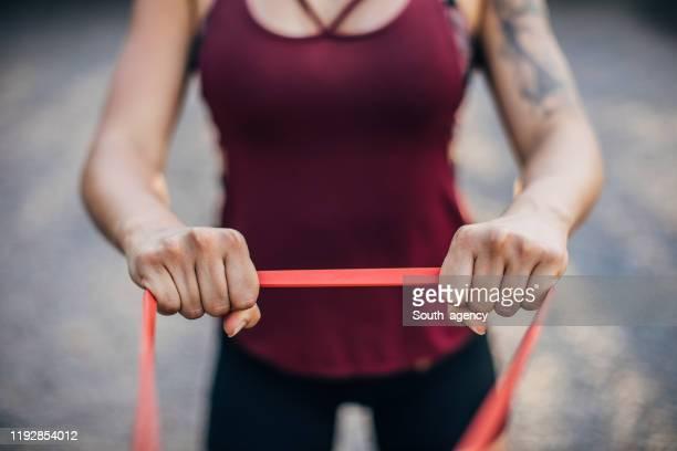公園で運動する美しい若い女性。 - ゴム ストックフォトと画像