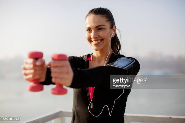 Beautiful young woman exercising with dummbells by river