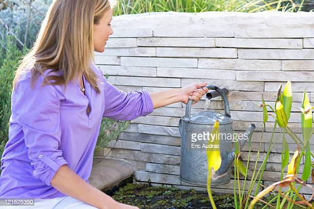 Beautiful young woman filling watering can with water