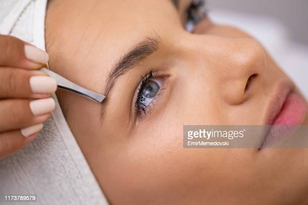 beautiful young woman gets eyebrow correction procedure - eyebrow stock pictures, royalty-free photos & images