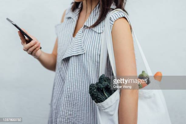 beautiful young woman grocery shopping with reusable shopping bag - wellness stock pictures, royalty-free photos & images