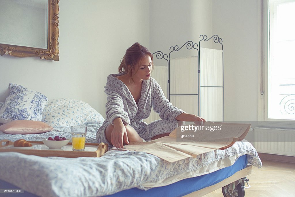 Beautiful young woman having breakfast and reads newspaper on be : Stock Photo