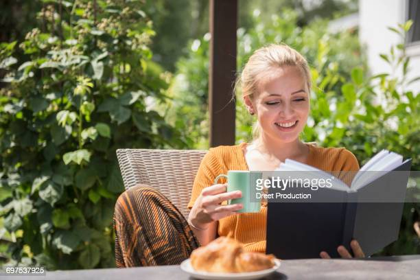 Beautiful young woman having cup of tea and reading book in the domestic garden, Munich, Bavaria, Germany