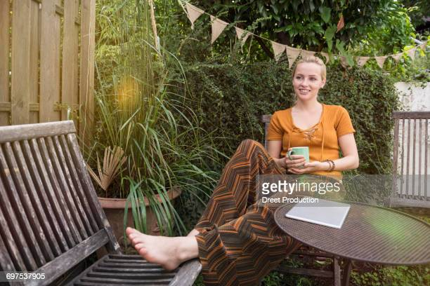Beautiful young woman having cup of tea in the domestic garden, Munich, Bavaria, Germany