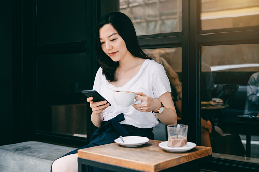 Beautiful young woman having some quiet time relaxing in cafe drinking coffee and using mobile phone - gettyimageskorea
