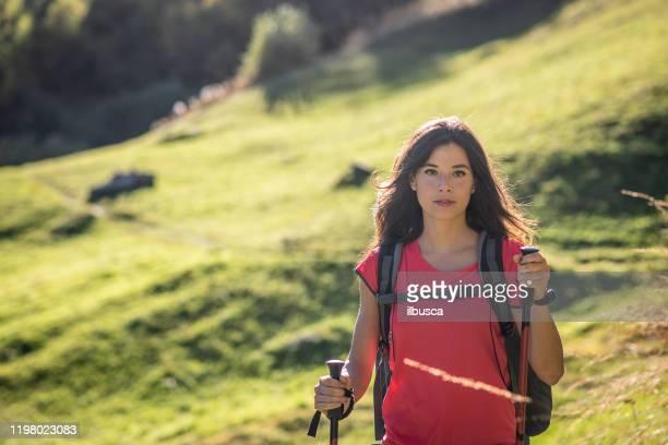 beautiful young woman hiking on italian alps mountains - ilbusca foto e immagini stock