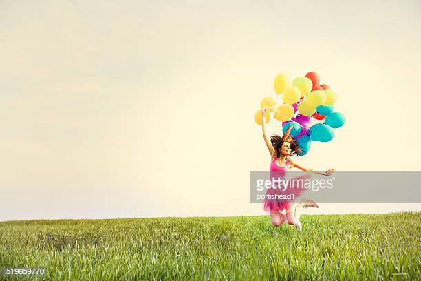 Bela jovem mulher segurando balões e saltar no campo
