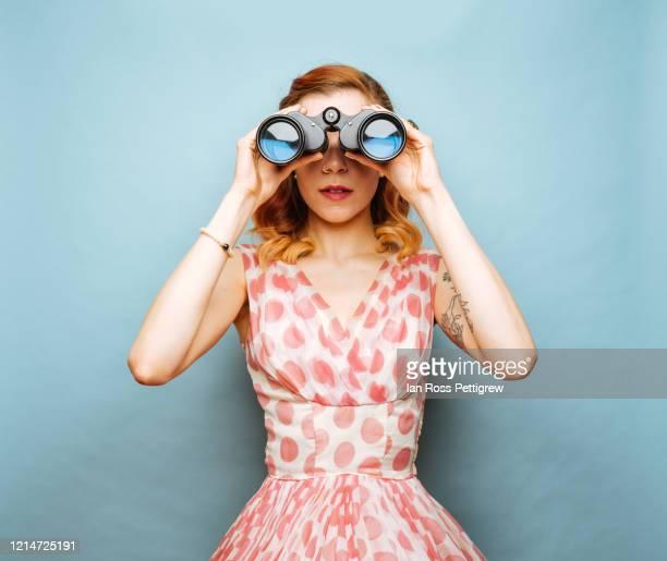 beautiful young woman holding binoculars - verrekijker stockfoto's en -beelden