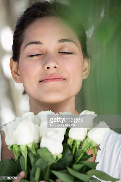 Beautiful young woman holding bunch of white flowers with her eyes closed