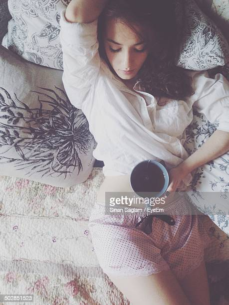 Beautiful young woman holding coffee cup while resting in bed