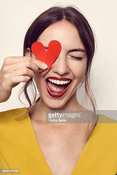 beautiful young woman holding heart over her eye