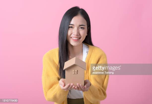 beautiful young woman holding house model - real estate loan concept - mortgage stock pictures, royalty-free photos & images