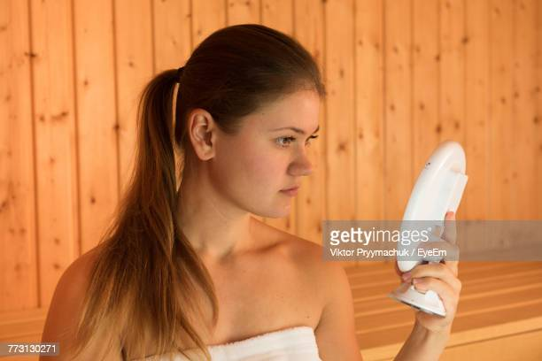 Beautiful Young Woman Holding Mirror While Sitting In Sauna